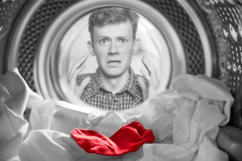 Red sock in white washing load with concerned man staring into washing machine